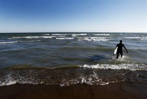 A surfer walks into the cold waves on Lake Ontario at a Toronto beach in this file photo.
