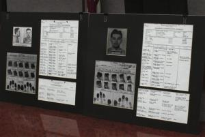 This photo from Tuesday, Dec. 18, 2012, shows a display of prison records for Richard Hickock, left, and Perry Smith, used at a news conference in Lansing, Kan.