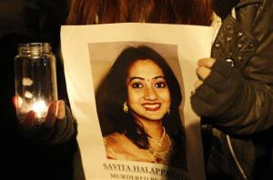 A woman holds a picture of Savita Halappanava during a vigil in Ireland. Halappanava died of blood poisoning after suffering a miscarriage.