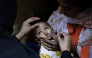 A Pakistani child receives a polio vaccine from a health worker in a Christian neighborhood in Islamabad, Pakistan, Tuesday, Oct. 16, 2012.