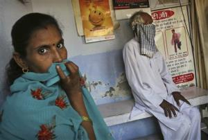 In this Monday, Oct. 22, 2012 photo, tuberculosis patients wait for medication with their faces covered at an Operation ASHA program center in New Delhi, India.