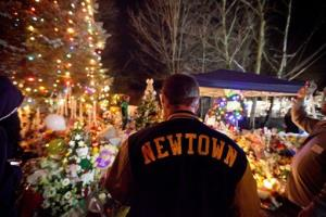 Greg Frattaroli, 19, of Newtown, Conn., visits a memorial for the Sandy Hook Elementary School shooting victims, Tuesday, Dec. 18, 2012, in Newtown, Conn.