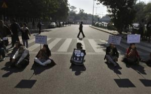 Indian protesters hold placards as they block a major traffic intersection during a protest in New Delhi, India, Wednesday.