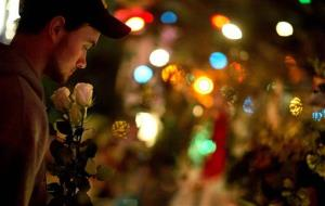 A Newtown resident holds roses as he visits a memorial for the Sandy Hook Elementary School shooting victims, Tuesday, Dec. 18, 2012, in Newtown, Conn.