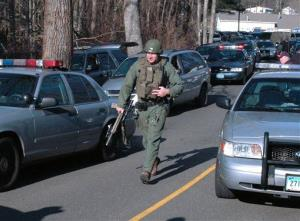 In this photo provided by the Newtown Bee, police officers are on the scene outside Sandy Hook Elementary School in Newtown on Friday, Dec. 14.