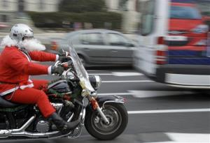 A motorcyclist wearing a Santa Claus suit rides in downtown Belgrade, Serbia, Saturday, Dec. 24, 2011.