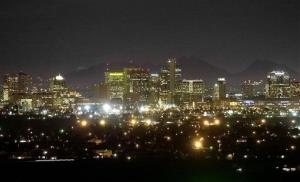 The Squaw Peak Mountains are seen behind the illuminated Phoenix skyline in this file photo.