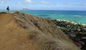 A hiker looks out over Kailua Bay on the Hawaiian island of Oahu.