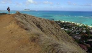 A hiker looks out over Kailua Bay on the Hawaiian island of Oahu.