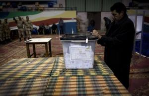 An Egyptian election worker controls a ballot box at a polling station in Giza, Egypt, Saturday, Dec. 22, 2012.