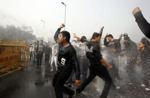 Indian protesters shout as policemen use water cannon to disperse those demonstrating against a gang rape and brutal beating of a 23-year-old student, in New Delhi, India, Sunday, Dec. 23, 2012.