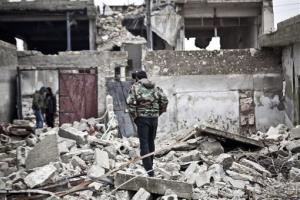 Free Syrian Army fighters walk amid the ruins of a village situated a short distance from an area where fighting between rebels and government forces continues, Saturday, Dec. 22, 2012.
