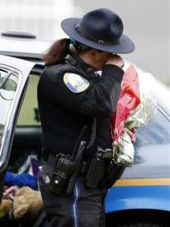 Newtown Police Officer Maryhelen McCarthy wipes away tears while placing flowers at a makeshift memorial outside of St. Rose of Lima Roman Catholic Church on Dec. 16.