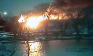 This image taken from WHAM13-TV, shows homes on fire in an area where a gunman ambushed four volunteer firefighters early Monday, Dec. 24, 2012, in Webster, NY.