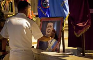 In this Thursday, Dec. 13, 2012 file photo, a member of Venezuela's navy touches an image of Venezuela's President Hugo Chavez.