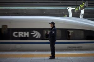 A policeman watches while a CRH high-speed train leaves the Beijing West Railway Station.