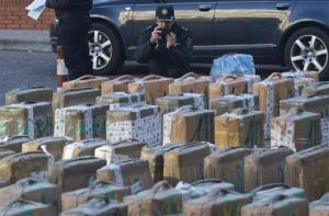 A police officer takes a photo on his cell phone of part of a haul of hashish and marijuana in Madrid.