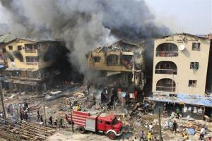 A fire truck passes a warehouse on fire on Lagos Island in Lagos, Nigeria, on Wednesday, Dec. 26, 2012.