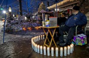 Members of a group monitoring memorials around the clock take an early morning shift Tuesday, Dec. 25, 2012, in Newtown, Conn.
