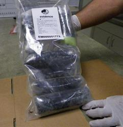In this Sept. 7, 2012, photo a US Drug Enforcement Administration technician holds several pounds of Mexican meth confiscated in the St. Louis area.
