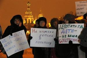 Opposition activists hold posters reading Do not involve children in politics and Lawmakers, children are not your  ownership during a protest against a bill banning US adoptions of Russian children in St. Petersburg, Russia, yesterday.