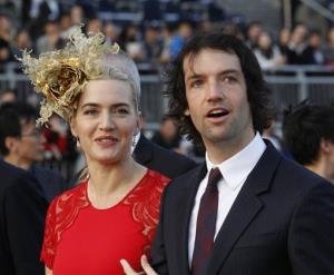 British actress Kate Winslet, left, arrives with Ned Rocknroll at the awards presentation of The Longines Hong Kong Cup horse race at the Shatin race track in Hong Kong, Sunday, Dec. 9, 2012.