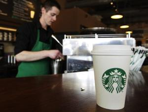 In this Friday, April 27, 2012, photo, a Starbucks drink waits for a customer to pick it up as barista Josh Barrow prepares another.