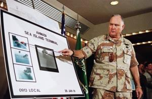 In this Jan. 27, 1991, file photo, U.S. Army Gen. Norman Schwarzkopf points to a row of photos of Kuwait's Ahmadi Sea Island Terminal on fire after a U.S. attack on the facility.