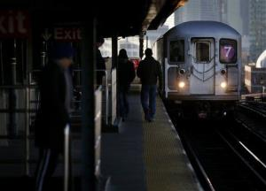 Commuters  walk on the platform as a train enters the 40th St-Lowry St Station, where a man was killed Friday.