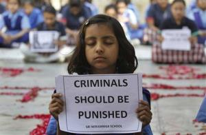A schoolgirl holds a placard during a prayer ceremony to mourn the death of a 23-year-old gang rape victim, at a school in Ahmadabad, India, Saturday, Dec. 29, 2012.