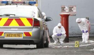 Police forensic officers examine the scene of a bomb attack outside a gambling shop in west Belfast, Northern Ireland, Saturday, Nov. 6, 2010.