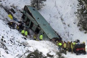 Emergency personnel respond to the scene of a multiple-fatality accident after a tour bus careened through a guardrail along an icy highway and fell several hundred feet down a steep embankment.
