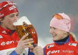 Ekaterina Iourieva, left, and Dmitri Iarochenko from Russia celebrate with a glass of beer after winning the Biathlon World Team Challenge.