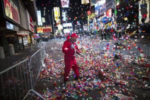 A worker clears confetti from a sidewalk in Times Square after midnight on New Years Tuesday Jan. 1, 2013, in New York.