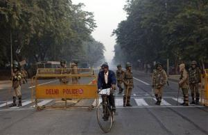 An Indian cyclist rides past policemen standing guard at a check point after security was beefed up following the death of a young woman who was gang-raped in a moving bus.