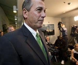 John Boehner passes waiting reporters as he leaves a closed-door GOP meeting on the fiscal cliff bill passed by the Senate Monday night, Jan. 1, 2013.