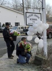 Volunteer firefighters place flowers at a makeshift memorial at a sign for the Sandy Hook Elementary school.