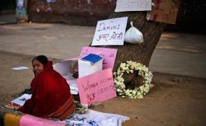 An Indian woman sits next to a tree that turned into a makeshift memorial for a gang rape victim in New Delhi, India, Thursday, Jan. 3, 2013.