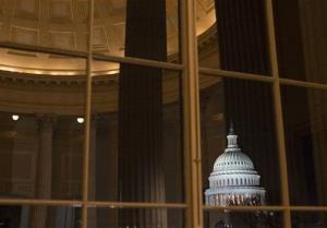 The US Capitol is seen amid reflections from inside the Cannon House Office Building on the last day of the 112th Congress.