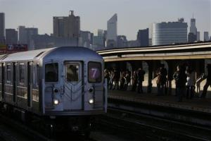 Commuters wait on the platform as a train passes through the 40th St-Lowry St Station, where a man was killed after being pushed onto the subway tracks, in the Queens section of New York, Friday, Dec. 28, 2012.