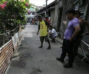 Neighbors look at the spot where a gunman, later identified as Ronald Bae, was killed by responding police following a shooting rampage in Kawit township, Jan. 4, 2013.
