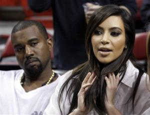 Kim Kardashian, right, and Kanye West, left, are shown before an NBA basketball game between the Miami Heat and the New York Knicks in this Dec, 6, 2012 file photo.