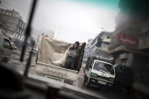 A boy is seen through a car window as he rides on the back of a truck in the streets of Aleppo, Syria, Saturday, Jan. 5, 2013. The revolt against President Bashar Assad that started in March 2011 began with peaceful protests but morphed into a civil war that has...