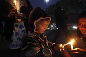 A young boy participates in a candlelight vigil protesting against a leader of the ruling Congress party accused of rape, in Gauhati, India, Friday, Jan. 4, 2013.