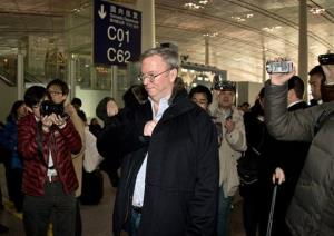 Google's executive chairman Eric Schmidt, center, is chased by journalists as he prepares to check in at the Beijing Capital International Airport today.