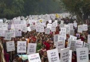 In this Wednesday, Jan. 2, 2013 file photo, Indian women carry placards as they march to mourn the death of a gang rape victim in New Delhi, India.