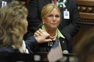 DebraLee Hovey grabs the hand of colleague Laura Hoydick after speaking at a service for the victims of the Sandy Hook Elementary School shooting at the state Capitol in Hartford, Conn., Dec. 19, 2012.