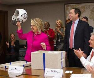 This handout photo provided by the State Department shows Secretary of State Hillary Rodham Clinton holding up a football helmet presented to her at the State Department.