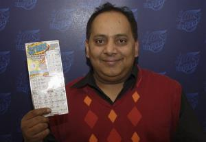 This photo provided by the Illinois Lottery shows Urooj Khan, 46, of Chicago's West Rogers Park neighborhood, posing with a winning lottery ticket.