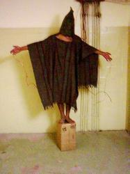An unidentified detainee stands on a box with a bag on his head and wires attached to him in late 2003 at the Abu Ghraib prison in Baghdad, Iraq.